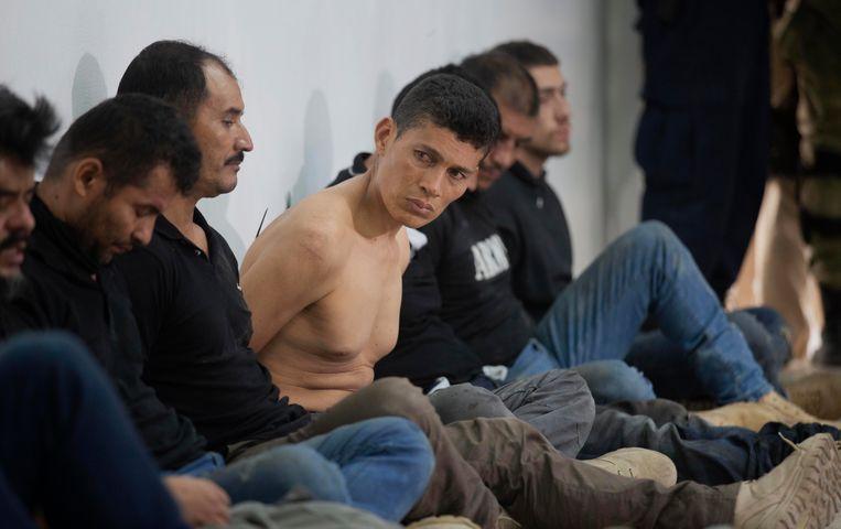 Opgepakte verdachten van de aanslag zitten geboeid op de grond bij de personferentie van 8 juli over de moord op president Jovenel Moïse. Beeld AP