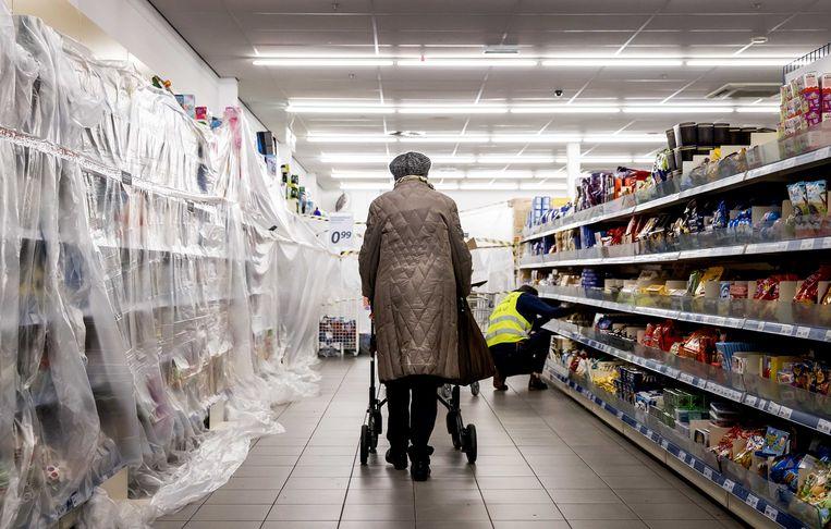 Een klant in de Action eerder deze week, met plastic over alle niet-essentiële producten. Beeld ANP