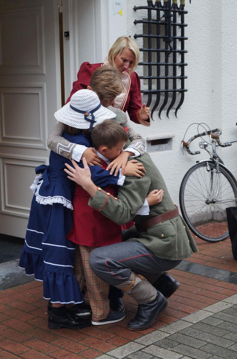 De plicht roept. Een soldaat neemt afscheid van zijn bedroefde gezin in de Neerstraat.