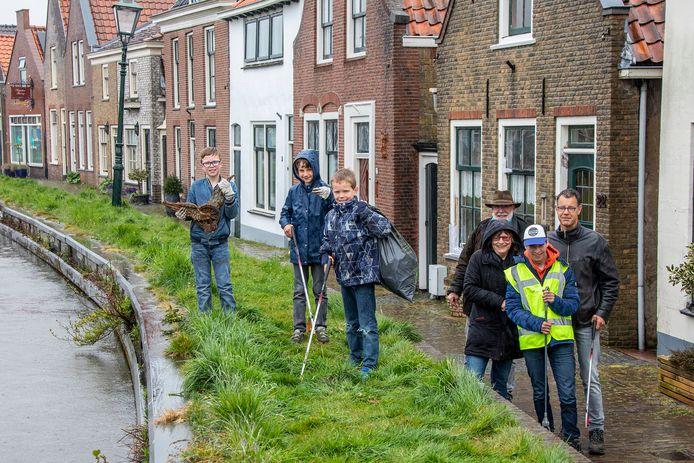 Jongeren met prikstokken en een gevonden oud onderdeel van een ANWB-bord. Op de achtergrond met Jan Holtkamp.