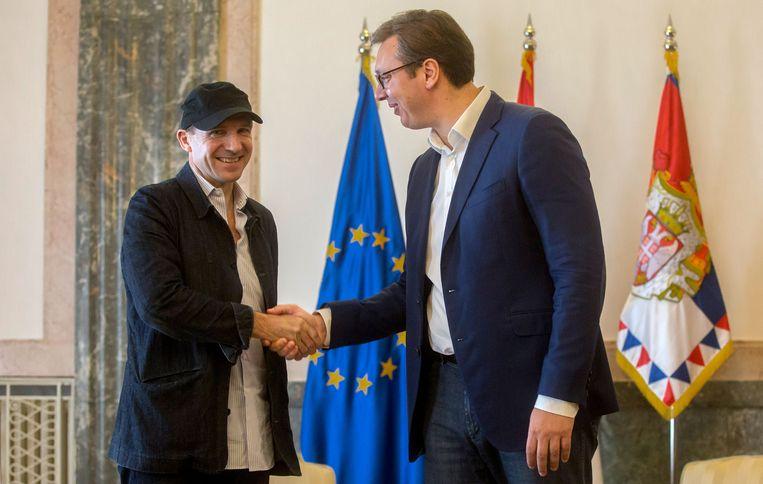 Ralph Fiennes (L) schudt Servisch president Aleksandar Vucic de hand. Beeld AFP