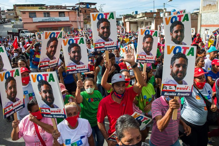 Onder de kandidaten voor het parlement ook Maduro's zoon Nicolás Ernesto, die er op de campagnefoto enthousiaster uitziet dan zijn aanhangers. Beeld AFP
