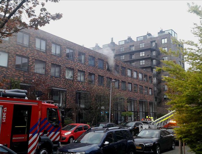De rook trekt de woningen in boven de parkeergarage.