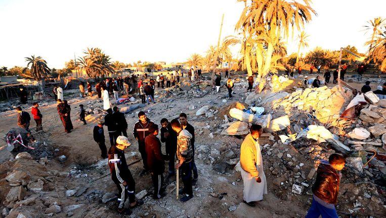 Libiërs verzamelen zich op het terrein van een gebombardeerd IS-trainingskamp in de buurt van de stad Sabratha, in 2016. Beeld afp