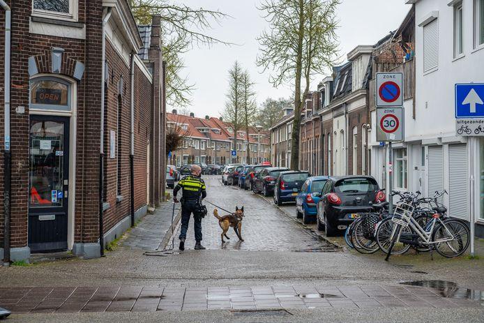 Met een politiehond wordt gezocht naar sporen rond de telefoonwinkel in Tilburg