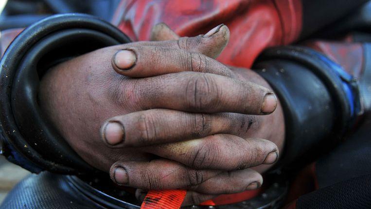 De handen van een duiker zitten onder de olie. Beeld getty