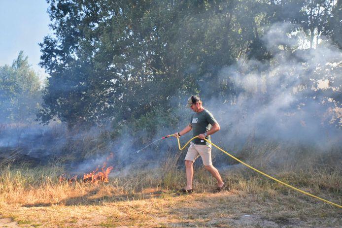 Buurtbewoners helpen met blussen bij de brand in de Tilburgse wijk Reeshof.