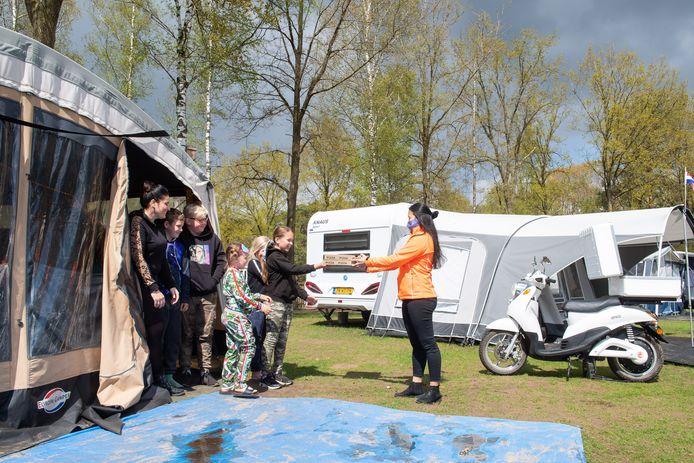 Bezorgster Body Benigno brengt op de camping op een elektrische scooter de maaltijden rond, in dit geval pizza's.