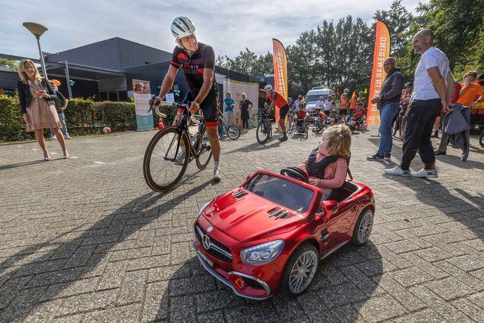 Michael Boogerd rijdt een rondje met de 2-jarige Tess van Loon in haar eigen elektrische auto.