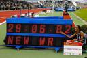 Sifan Hassan bij het bord met haar pas gelopen wereldrecordtijd op de 10.000 meter.