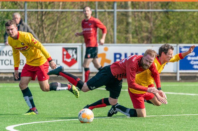 Ties Heutinck (rood shirt) gaat onderuit namens SC Bemmel tegen Rohda Raalte.