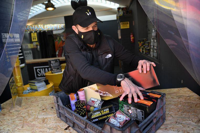Een vuurwerkhandelaar in Baarle-Hertog maakt een pakket klaar voor verkoop.  Beeld Marcel van den Bergh / de Volkskrant