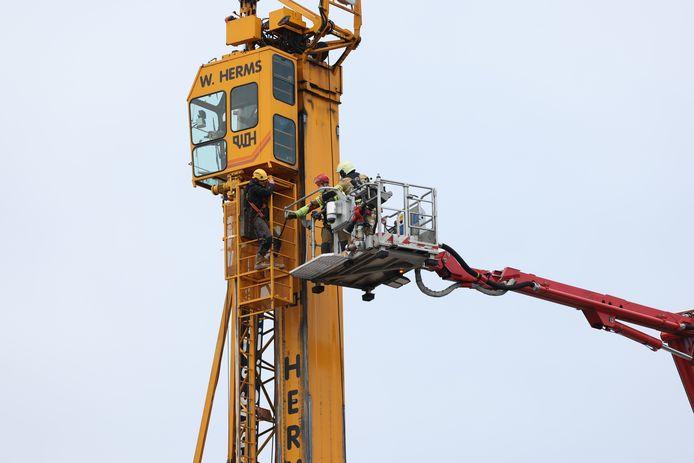De machinist klautert uit zijn cabine en wordt met een hoogwerker naar beneden gebracht.