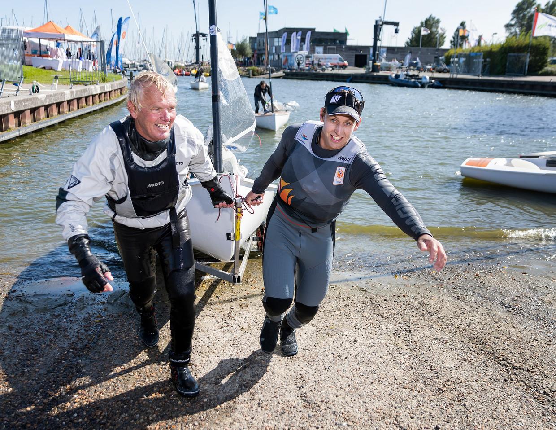 Zoon Nicholas Heiner helpt zijn vader Roy met het uit het water trekken van de boot, in Medemblik, Nederland. Beeld Jiri Büller