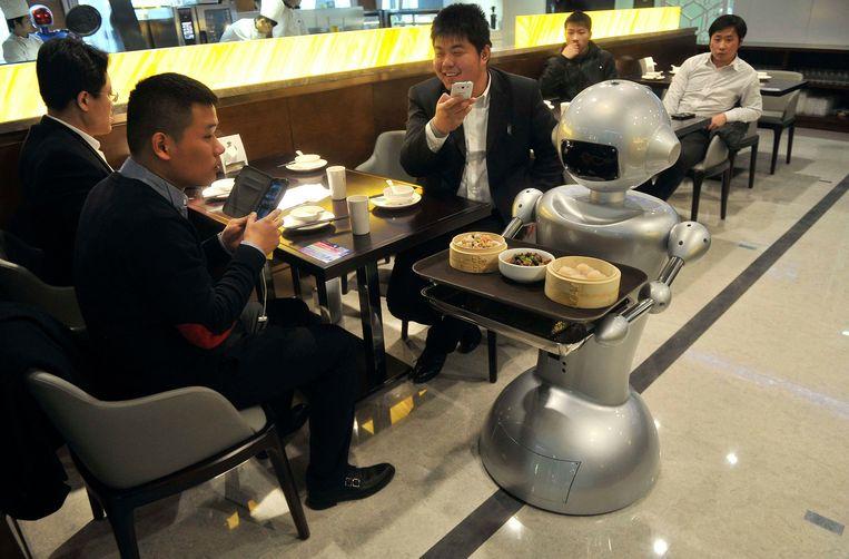 ...en leveren het eten af bij de klanten aan tafel. Die vervolgens geamuseerd foto's maken. Beeld REUTERS