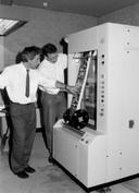 Louis van den Meijdenberg (links) bekijkt in 1995 samen met een collega hoe foto's uit de ontwikkelmachine komen