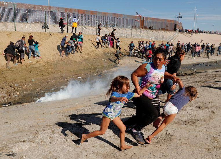 Een moeder gaat met haar twee kinderen op de loop voor traangas aan de grens tussen Mexico en de VS. Beeld REUTERS