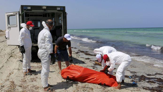Libische reddingswerkers bergen het lichaam van een van de slachtoffers van de bootramp voor de kust van Zuwara