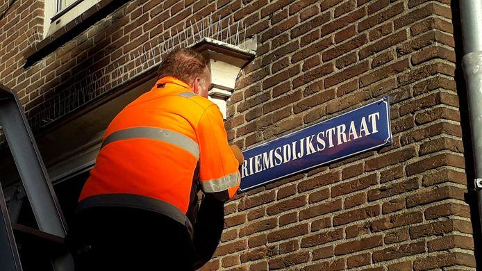 Een nieuw emaillen straatnaambord wordt aan de muur bevestigd aan de Riemsdijkstraat in Wageningen.