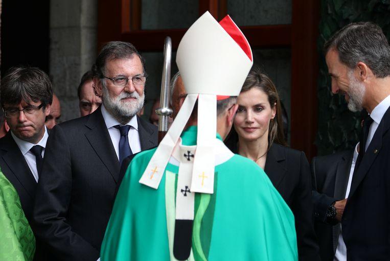 Aartsbisschop Juan José Omella (hier met links premier Rajoy) gispte tijdens de herdenkingsdienst politici die blijven ruziën. Beeld REUTERS