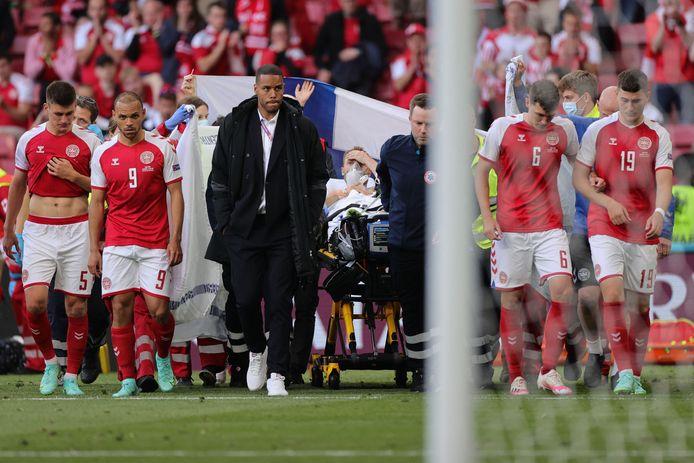 Christian Eriksen wordt van het veld begeleid door zijn ploeggenoten en de medische hulptroepen.