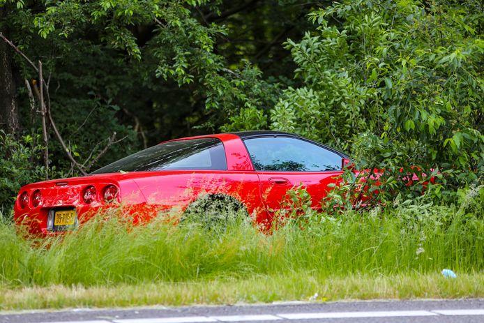 De rode Corvette die uit de bocht is gevlogen en bovenop een boomstronk belandde.