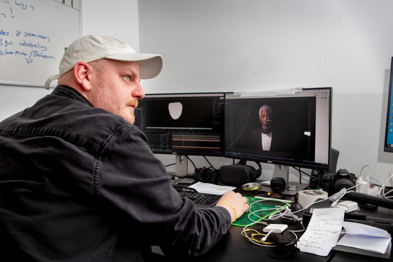 Bob de Jong werkt in zijn appartement in Amsterdam aan zijn deepfakevideo met Morgan Freeman.  Beeld Pauline Niks
