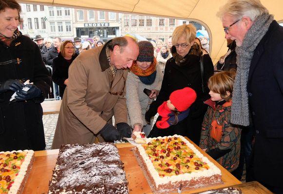 Burgemeester Frank Boogaerts snijdt een van de taarten aan.