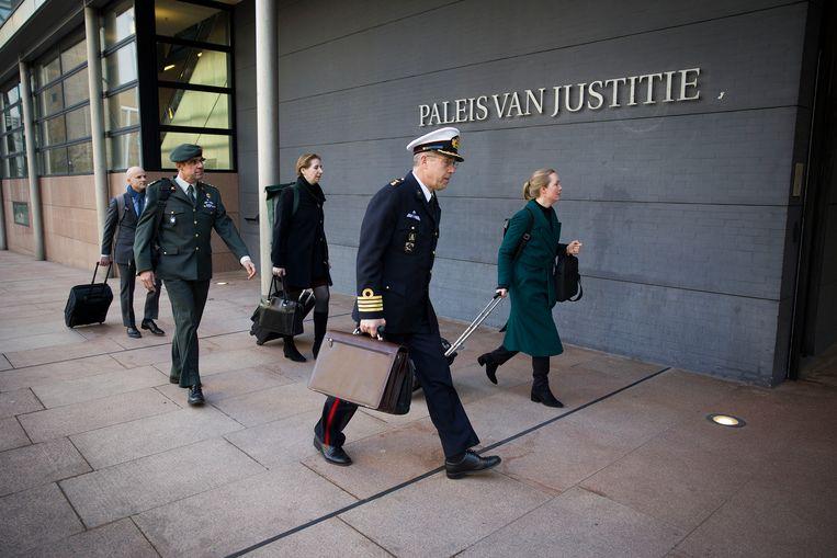 Militairen en advocaten komen aan bij de rechtbank in Den Haag waar maandag voor het eerst een rechter naar de Slag om Chora kijkt. Beeld Arie Kievit