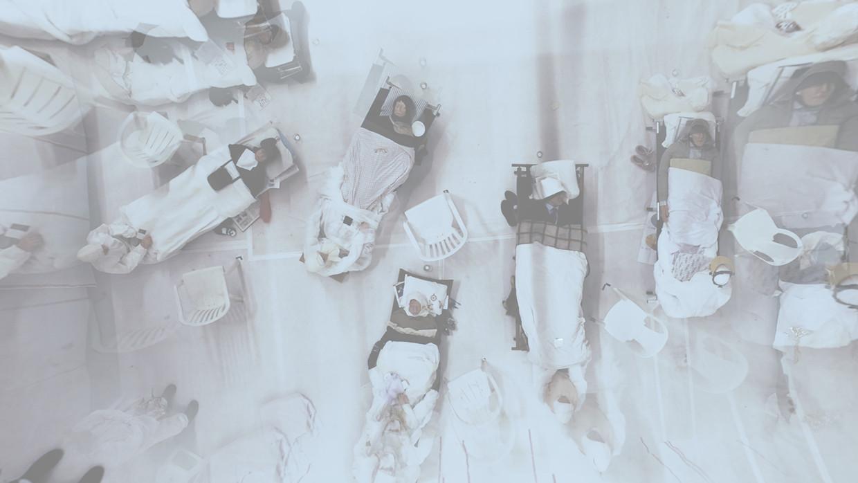 Veldbedjes met bewegingloze mannen en in het wit gehulde, schijnbaar over hen wakende verpleegsterfiguren. Beeld Holland Festival
