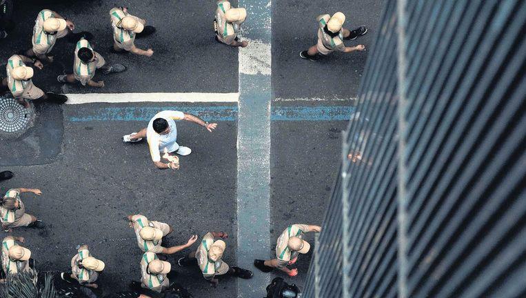 Omringd door een haag van veiligheidsmensen droegen verschillende sporters gisteren de olympische vlam door Rio de Janeiro. Beeld afp