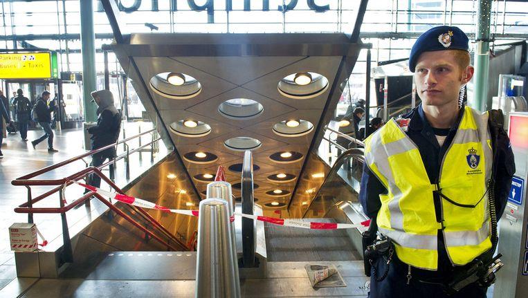 Een lid van de Koninklijke Marechaussee bewaakt in november 2010 op Schiphol de toegang naar het ondergrondse treinstation, omdat er in een trein bij een van de perrons brand was ontstaan. © ANP Beeld