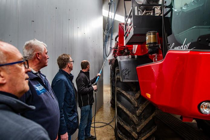 Wiljan Wiegink van Markvoort spuit een tractor af in de milieuvriendelijke wasstraat van het loonbedrijf in Averlo.