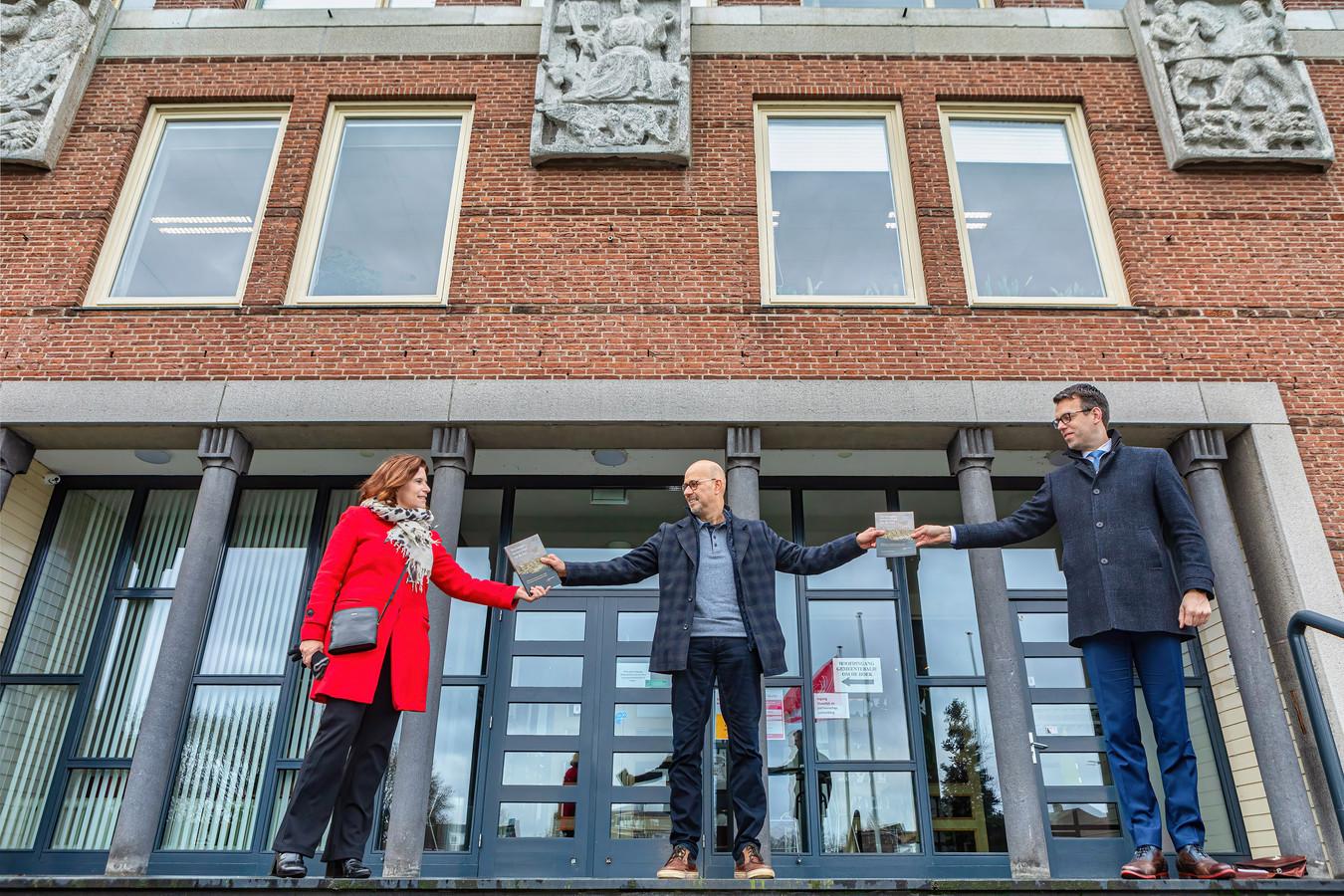 Burgemeester Derk Alssema (r.) en wethouder Ariane Zwarts namen voor het gemeentehuis de eerste exemplaren in ontvangst van het boek dat Kees van der Heijden (m.) heeft geschreven over het legerkamp bij Rijen tussen 1830 en 1839.