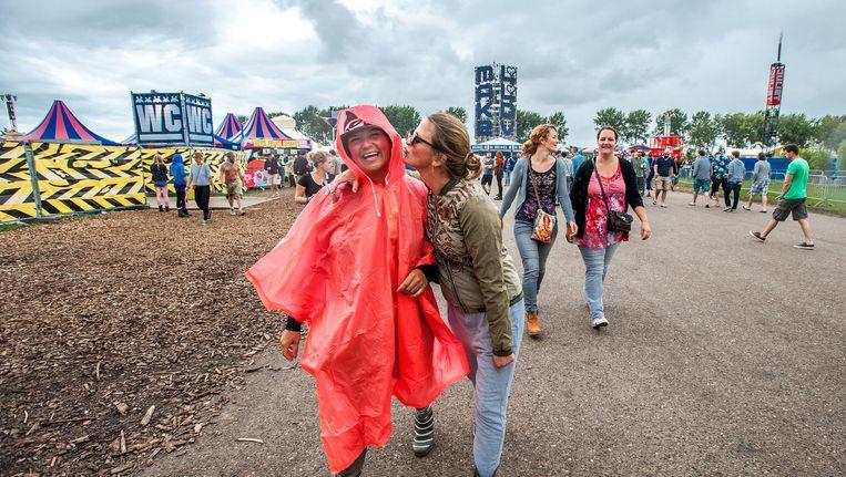 Festivalgangers met poncho en kaplaarzen op het op het terrein van Lowlands. Beeld anp