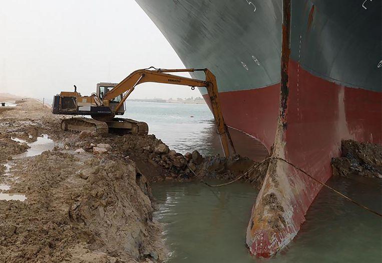 Met een graafmachine werd in eerste instantie geprobeerd de boeg van het schip vrij te graven uit de modder van de oever van het Suezkanaal. Ondertussen zijn gespecialiseerde Nederlandse ploegen ter plaatse. Beeld AFP
