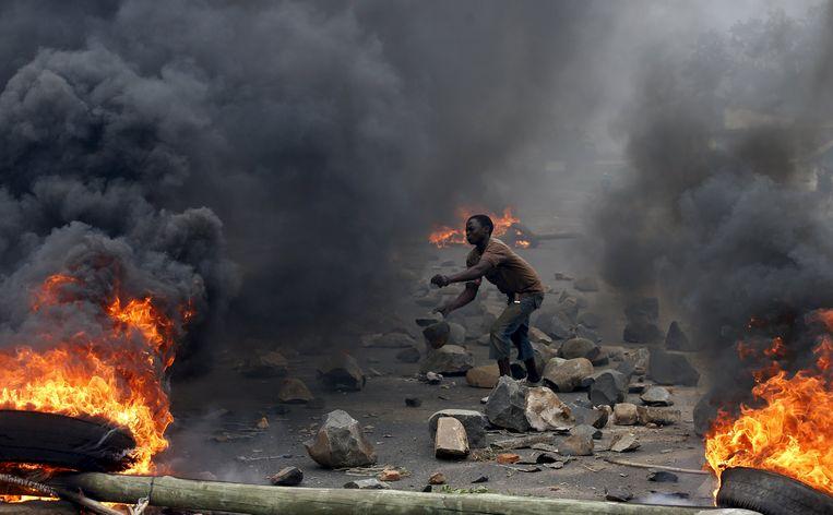 Een betoger gooit stenen tijdens een protestactie tegen de Burundese president Pierre Nkurunziza. Beeld REUTERS