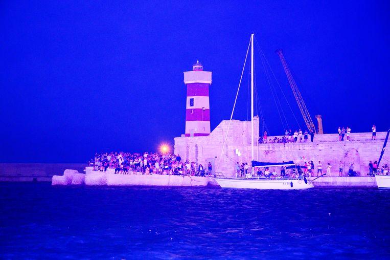 Wachten op de boot met de Madonna en de houten balken bij de vuurtoren van Monopoli. Beeld SANNE DE WILDE