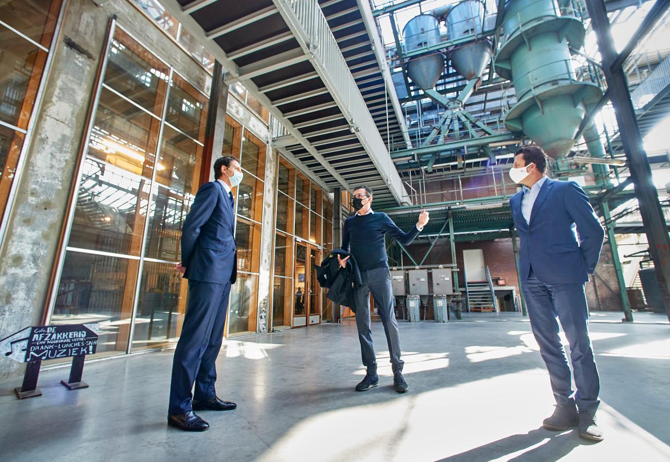 Minister Wopke Hoekstra (links)  krijgt een rondleiding door Stefan (midden) en Frank van de Ven op de Noordkade in Veghel.