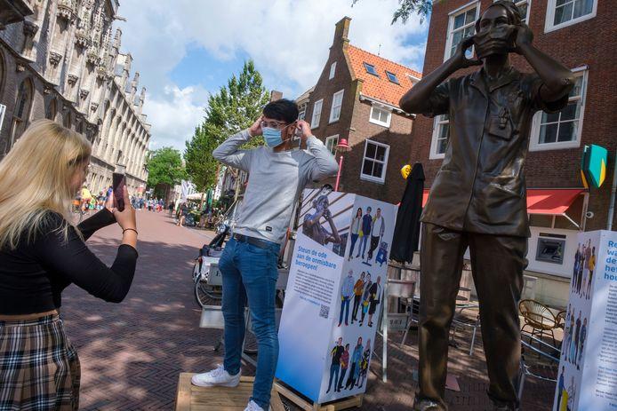 Grace Peters zet Julian Breuer op de foto bij het mobiele FNV-standbeeld Anique op de Markt in Middelburg.