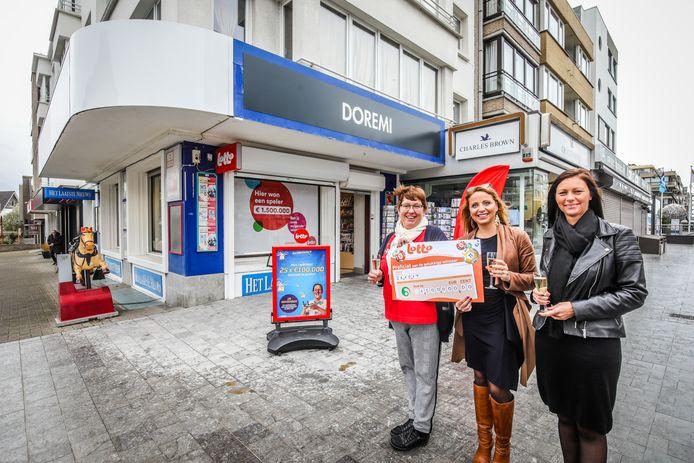 Patricia Desnoeck van dagbladhandel Do Re Mi neemt de cheque van de Nationale Loterij symbolisch in ontvangst.