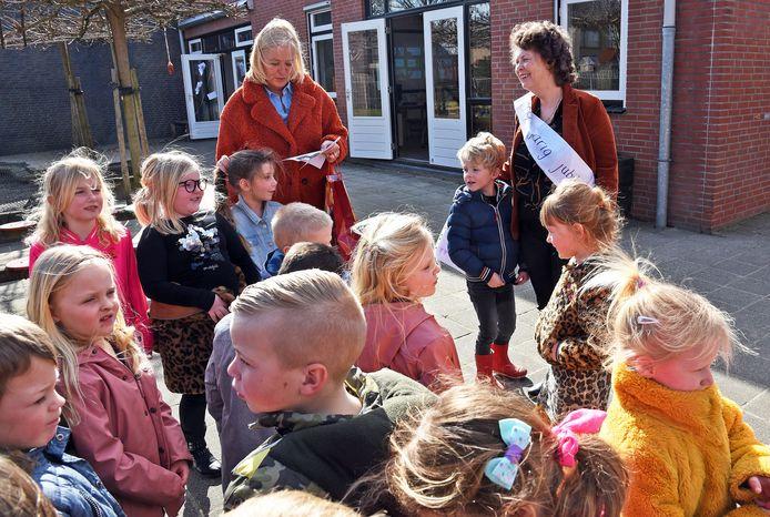 Directrice Nancy Warrens (rechts) luistert naar een gedicht van de kinderen van groep 1 en 2.  Met oranje jas Anja van Damme, leerkracht groep 1 en 2.
