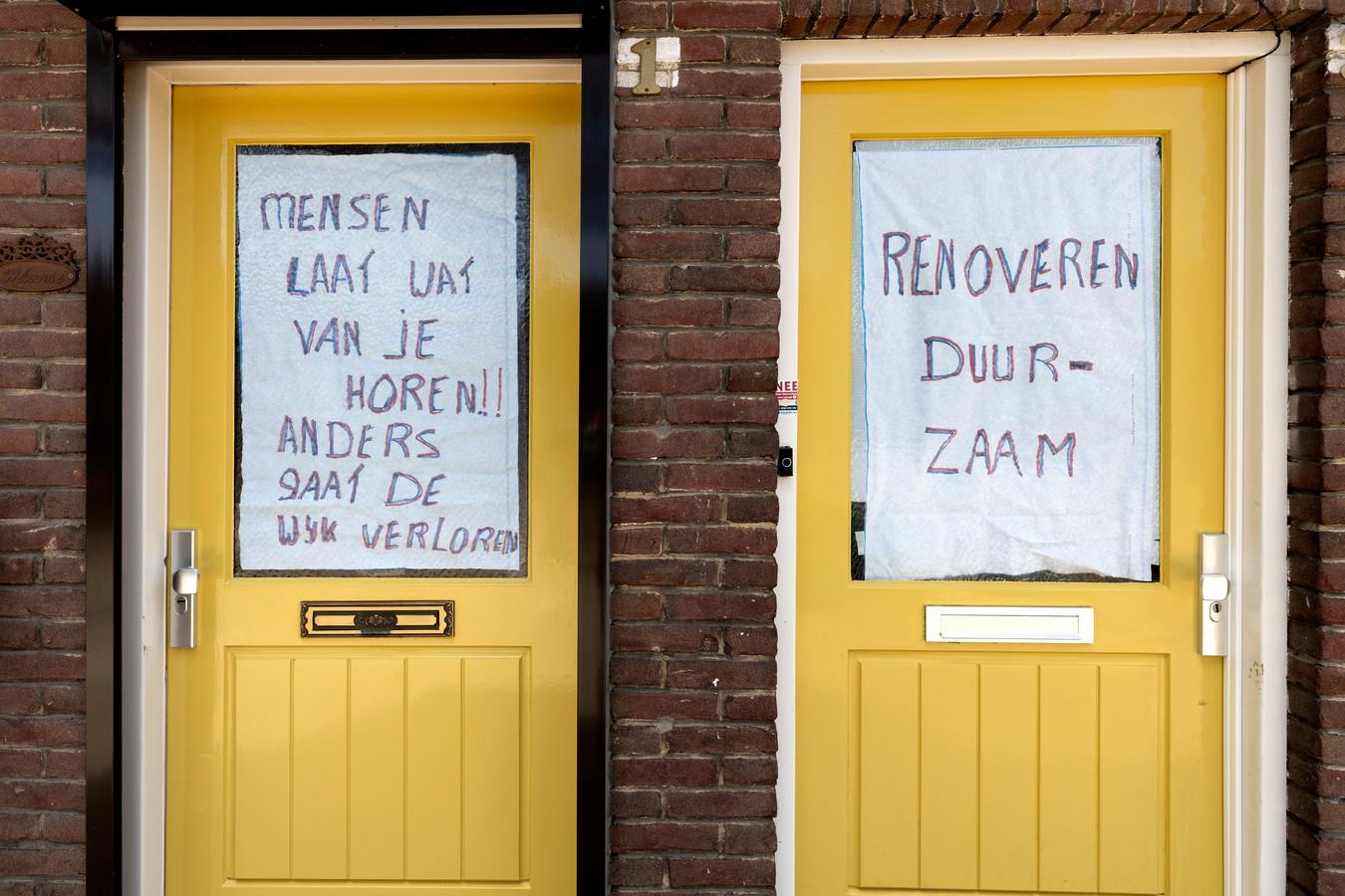 In de Gildebuurt in Eindhoven mochten bewoners kiezen tussen renoveren en sloop\nieuwbouw. Ondanks actieposters, zoals hier achter de voordeur aan de Wassenaarstraat, voor renovatie, werd het toch sloop.