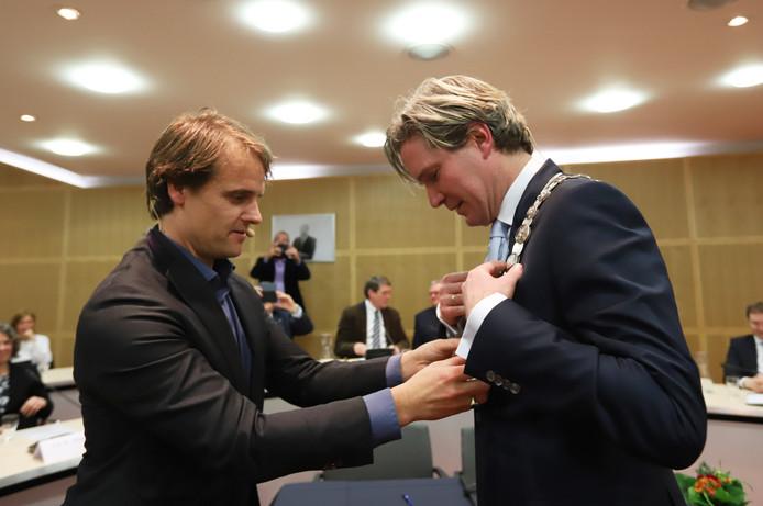 Martijn Hamerslag (l) hangt een trotse Foort van Oosten de ambtsketting om.