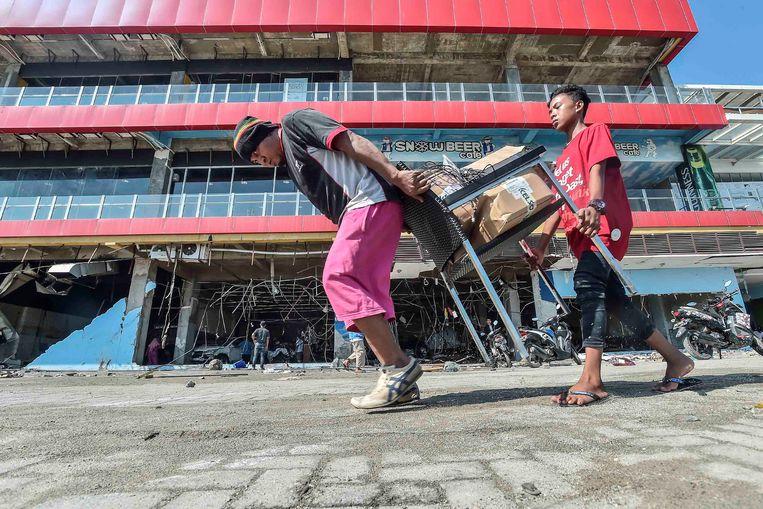 Inwoners van Palu met geplunderde goederen. Beeld REUTERS