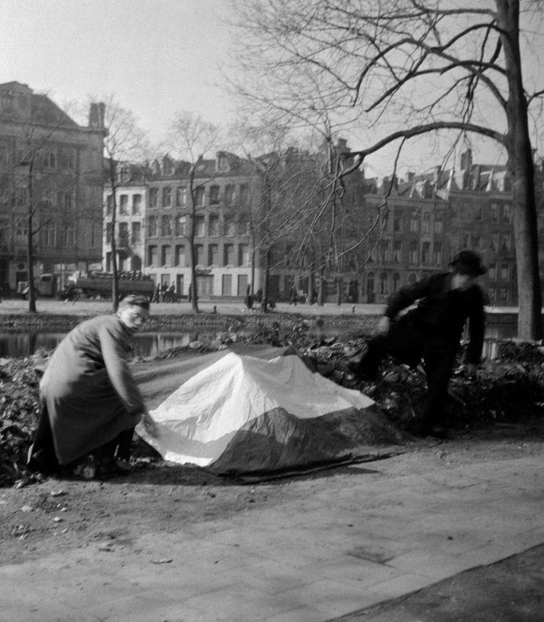 In het Eerste Weteringplantsoen wordt door de illegaliteit een Nederlandse vlag gelegd op de plek waar de bezetter een aantal dagen eerder dertig gevangenen heeft gefusilleerd. Beeld  Cas Oorthuys / Nederlands Fotomuseum