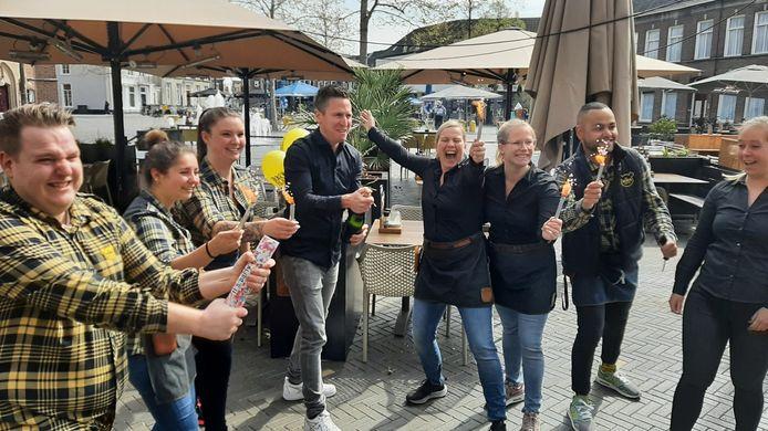Erik Oomes (midden) van het Oosterhoutse restaurant De Beren staat klaar voor het ontkurken van de fles champagne om de heropening van zijn terras luister bij te zetten.