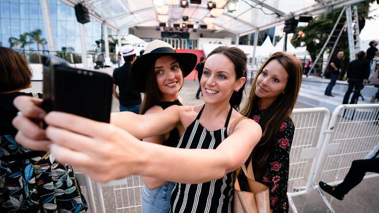 Toeristen nemen een selfie aan de rode loper in Cannes. Beeld Getty Images