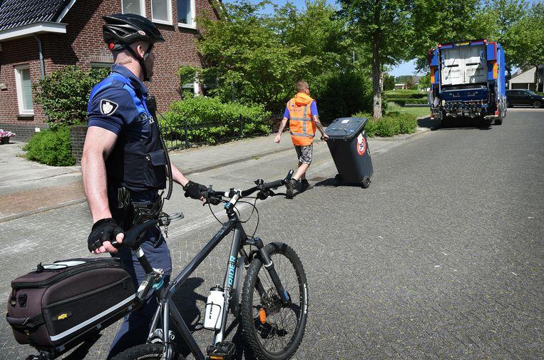 Ad van den Berk, buitengewoon opsporingsambtenaar (boa) van de gemeente Best, terwijl hij op zijn mountainbike achter de vuilniswagen aan fietst. Foto Marcel van den Bergh Beeld -