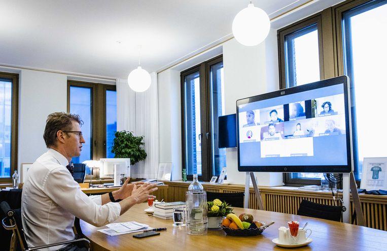 Sander Dekker, demissionair minister voor Rechtsbescherming, praat online met belangengroepen over het opschorten van interlandelijke adoptie.  Beeld ANP